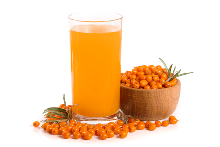 Sea buckthorn juice in a glass and wooden bowl with berries isolated on white background
