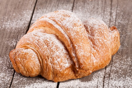 croissant sprinkled with powdered sugar on old wooden board