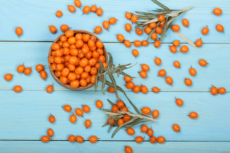 Sea buckthorn. Ripe fresh berries in bowl on blue wooden background. Top view