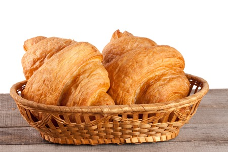 croissant in wicker basket on a wooden table with white background Stock Photo