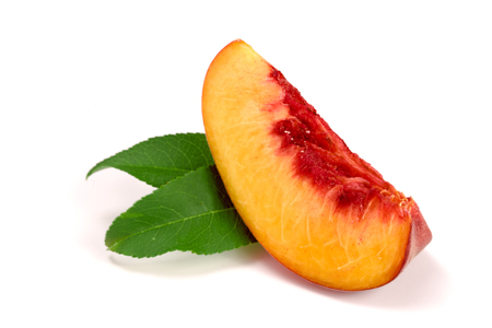 slice of peach with green leaf isolated on white background.