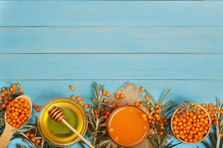 Sea buckthorn juice or tea with honey on a blue wooden background with copy space for your text. Top view,