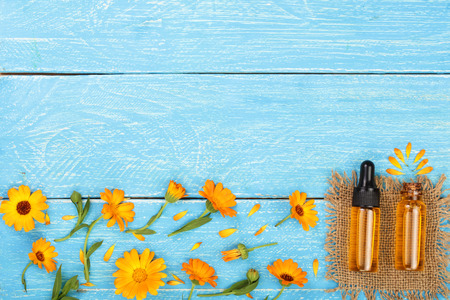 aromatherapy essential oil with marigold flowers on blue background with copy space for your text. Top view Stock Photo