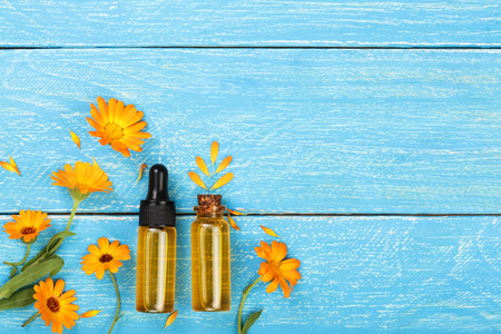 aromatherapy essential oil with marigold flowers on blue background with copy space for your text. Top view Zdjęcie Seryjne
