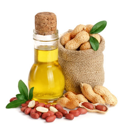 peanut oil in a glass bottle with peanuts in bag.