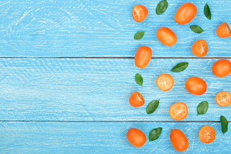 Cumquat or kumquat with leaf on blue wooden background with copy space for your text. Top view. Flat lay pattern.