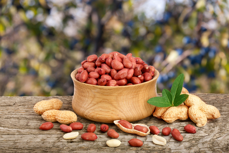 nutshells: peanuts with leaf in bowl on old on wooden table with a blurry garden background Stock Photo