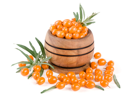 Sea buckthorn. Fresh ripe berry with leaves in a wooden bowl isolated on white background macro