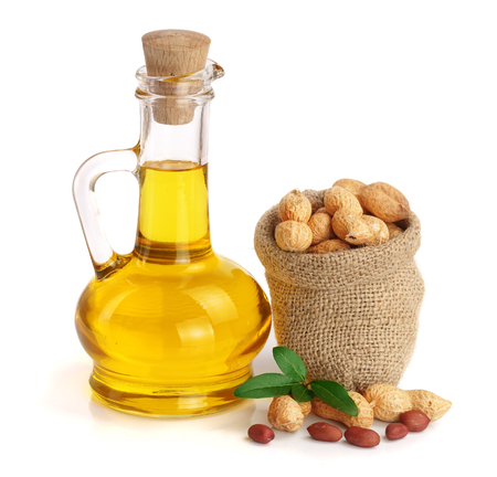 peanut oil in a glass bottle with peanuts in bag