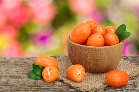 Cumquat or kumquat with leaf in wooden bowl on old wooden table with blurry garden background