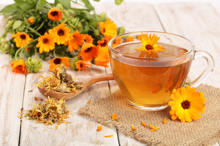pot marigold: Calendula tea with fresh and dried flowers on white wooden background