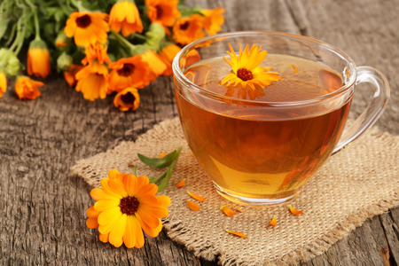Calendula tea with fresh flowers on old wooden background