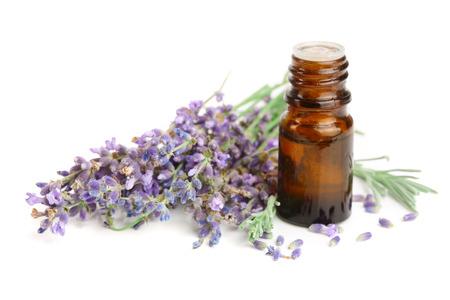 Fles met aromaolie en lavendelbloemen die op witte achtergrond worden geïsoleerd