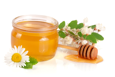 Jar of honey with flowers of acacia and chamomile isolated on white background. Stock Photo