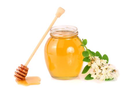 Jar of honey with acacia flowers isolated on white background