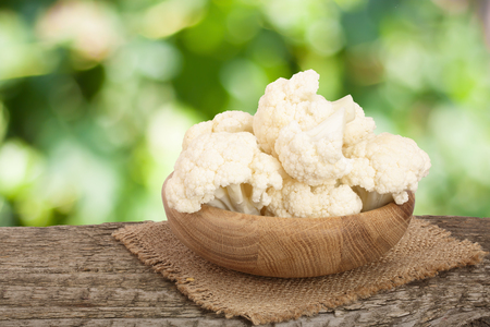 Piece of cauliflower in bowl on wooden table with blurred garden background Stockfoto