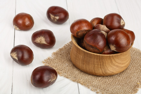 chestnut in wooden bowl on white wooden background.
