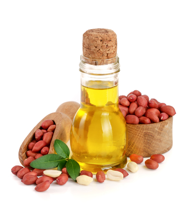 peanut oil in a glass bottle with peanuts in bowl.