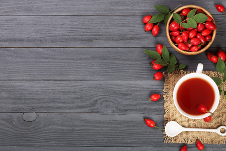tea with rose hips and honey on a black wooden background with copy space for your text. Top view
