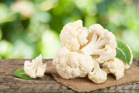Piece of cauliflower on wooden table with blurred garden background.