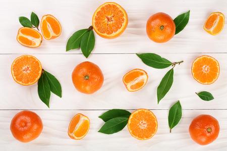 sinaasappel of mandarijn met bladeren op witte houten achtergrond. Plat leggen, bovenaanzicht. Samenstelling van het fruit