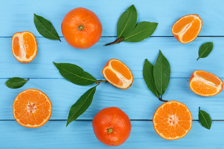 orange or tangerine with leaves on blue wooden background. Flat lay, top view. Fruit composition.