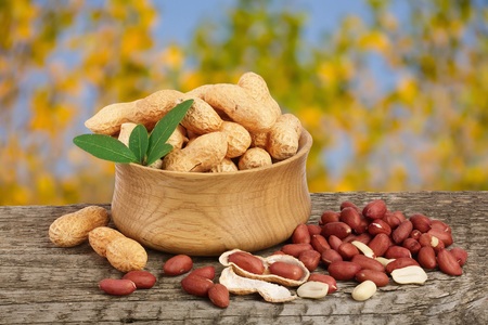 peanuts with leaf in bowl on old on wooden table with a blurry garden background Stock Photo
