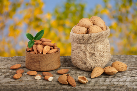 Almonds with leaf in bag from sacking on a wooden table with blurred garden background. Stock Photo