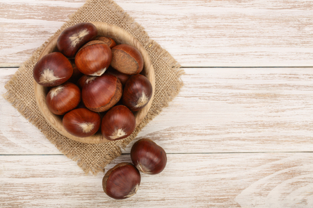 chestnut in bowl on white wooden background with copy space for your text. Top view. Flat lay. Stok Fotoğraf