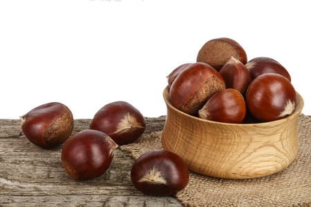 chestnut in bowl on the old wooden table with white background.