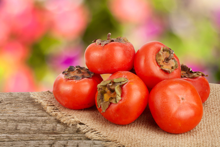 Persimmon fruit on wooden table with blurred garden background Stock Photo