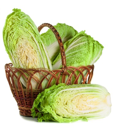 chinese cabbage and half in a wicker basket isolated on white background