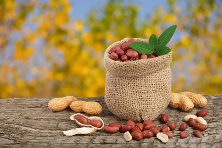 peanuts with leaf in bag on old on wooden table with a blurry garden background. Stock Photo