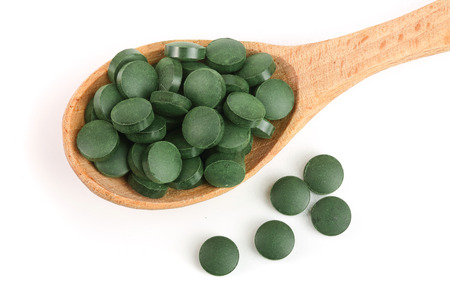 heap of Spirulina tablets algae nutritional supplement in wooden spoon isolated on white background close up top view. Flat lay.
