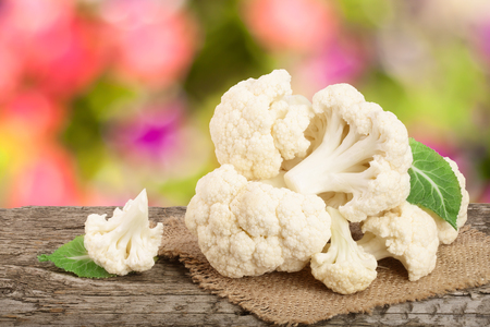 Piece of cauliflower on wooden table with blurred garden background.
