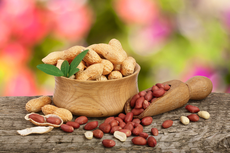 peanuts with leaf in bowl on old on wooden table with a blurry garden background. Stock Photo