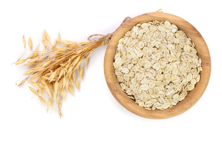 oat spike with oat flakes in wooden bowl isolated on white background.