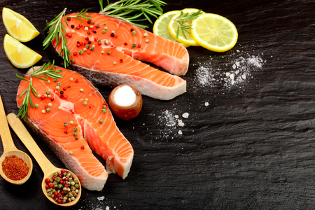 Slice of red fish salmon with lemon, rosemary and peppercorns on black stone background with copy space for your text. Top view