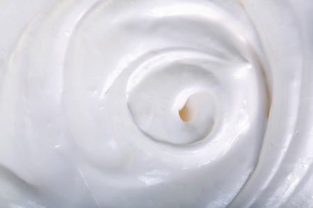 close up of a white whipped or sour cream on white background.