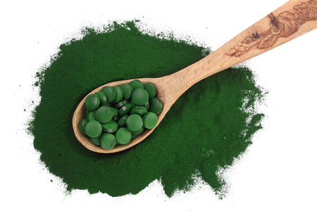 Spirulina algae powder and pills in wooden spoon isolated on white background. Top view. Stockfoto