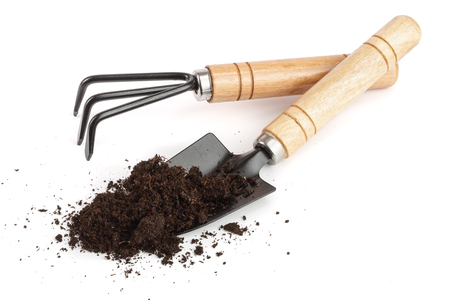 garden tools in soil isolated on white background.