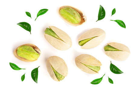 Pistachios decorated with green leaves isolated on white background, top view. Flat lay.