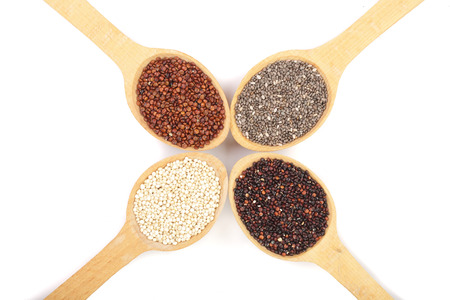 Black red white quinoa and chia seeds in wooden spoon isolated on white background. Top view.