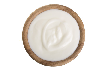 yogurt in a wooden bowl isolated on white background top view.