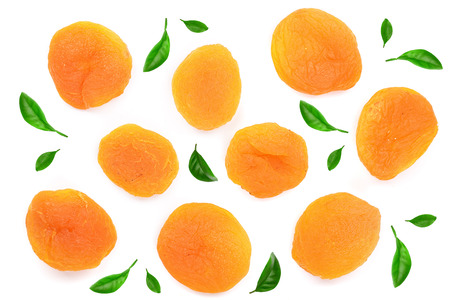 Dried apricots decorated with green leaves isolated on a white background. Top view. Flat lay pattern.