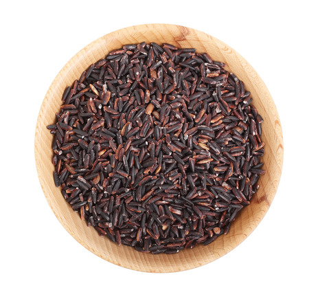 black rice grains in wooden bowl isolated on white background. Top view. Flat lay