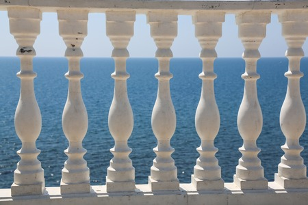 Baluster beach. White columns overlooking the sea. View of white pillars and horizont on blue sea and the sky in the background.