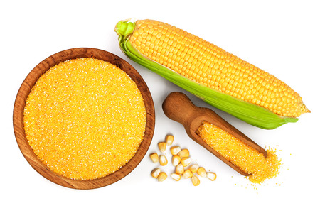 corn groats or cornmeal in wooden bowl and corncob isolated on white background. Top view. Flat lay.
