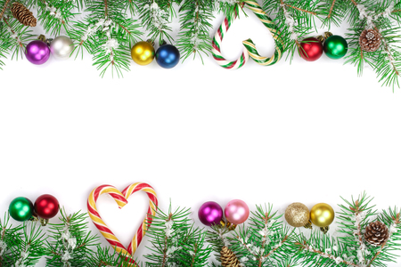 Christmas Frame of Fir tree branch with candy canes and balls isolated on white background with copy space for your text. Top view.
