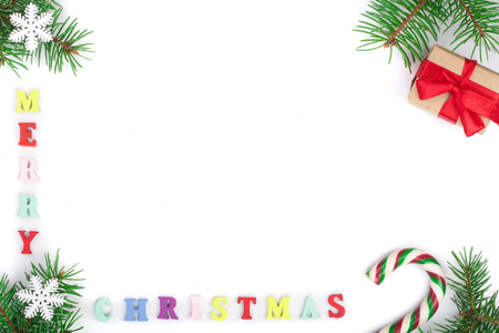 merry christmas inscription in frame made of fir branches, festive decorations isolated on white background with copy space for your text. Christmas background. Flat lay. top view.